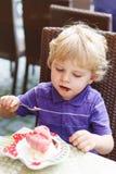 Niño pequeño rubio precioso que come el helado en café de la ciudad en verano Imagen de archivo libre de regalías