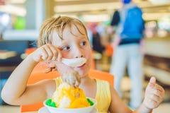 Niño pequeño rubio precioso que come el helado en café de la ciudad en verano Foto de archivo libre de regalías