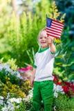 Niño pequeño rubio sonriente que celebra la bandera americana y agitarla Imágenes de archivo libres de regalías