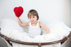 Niño pequeño, sentándose en una silla grande Imágenes de archivo libres de regalías