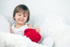 Niño pequeño, sentándose en una silla grande Fotos de archivo libres de regalías