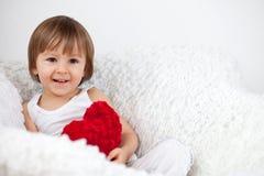 Niño pequeño, sentándose en una silla grande Foto de archivo