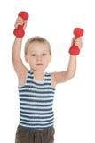 Niño pequeño serio con pesas de gimnasia Imágenes de archivo libres de regalías