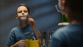 Niño pequeño serio que afeita en espejo almacen de metraje de vídeo