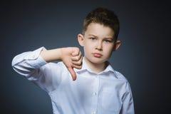 Niño pequeño serio que se sostiene el pulgar abajo en fondo gris Imagenes de archivo