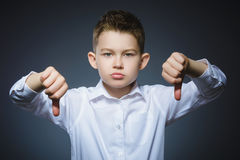 Niño pequeño serio que se sostiene el pulgar abajo en fondo gris Fotografía de archivo libre de regalías
