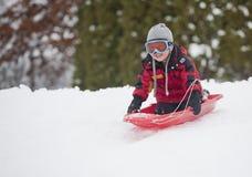 Niño pequeño sledding. Fotografía de archivo