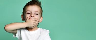 Niño pequeño soñoliento que bosteza y que mira la cámara aislada fotografía de archivo