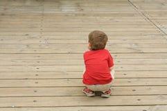 Niño pequeño en una acera Foto de archivo libre de regalías