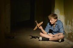 Niño pequeño solo en un sótano oscuro Fotografía de archivo