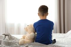 Niño pequeño solo que se sienta en cama en sitio Imagen de archivo libre de regalías