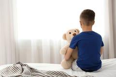 Niño pequeño solo que se sienta en cama en sitio Imagen de archivo