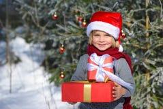 Niño pequeño sonriente con el bosque del invierno de los regalos im de la Navidad Fotos de archivo libres de regalías