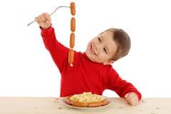 Niño pequeño sonriente con el encadenamiento de salchichas Imágenes de archivo libres de regalías