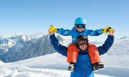Niño pequeño sonriente con el padre en las montañas durante día de fiesta del esquí Fotografía de archivo