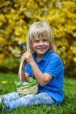 Niño pequeño sonriente con la cesta llena de huevos de Pascua coloridos al aire libre Fotos de archivo