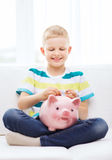 Niño pequeño sonriente con la hucha en casa Imagenes de archivo