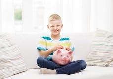 Niño pequeño sonriente con la hucha y el dinero Fotografía de archivo libre de regalías