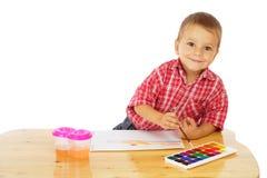 Niño pequeño sonriente con las pinturas de la acuarela Fotos de archivo