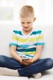 Niño pequeño sonriente con smartphone en casa Imagen de archivo libre de regalías
