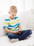 Niño pequeño sonriente con smartphone en casa Fotografía de archivo