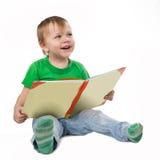 Niño pequeño sonriente con un libro que se sienta en el piso Imágenes de archivo libres de regalías