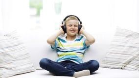 Niño pequeño sonriente en auriculares en casa almacen de video