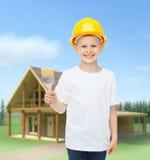 Niño pequeño sonriente en casco con la brocha Imagen de archivo libre de regalías