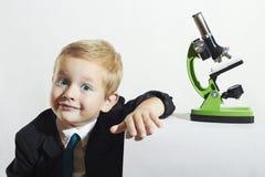 Niño pequeño sonriente en lazo Niño divertido Colegial que trabaja con el microscopio Cabrito elegante Imagen de archivo libre de regalías