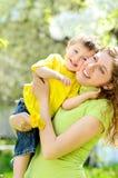 niño pequeño sonriente en los brazos de su madre fotos de archivo