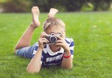 Niño pequeño sonriente feliz con la cámara retra del vintage Imagen de archivo libre de regalías