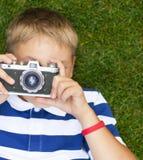 Niño pequeño sonriente feliz con la cámara retra del vintage Imagen de archivo