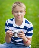 Niño pequeño sonriente feliz con la cámara retra del vintage Foto de archivo libre de regalías