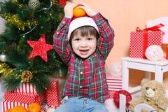 Niño pequeño sonriente feliz en el sombrero de Papá Noel con la mandarina Fotos de archivo libres de regalías