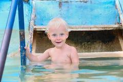 Niño pequeño sonriente feliz que entra en el agua en piscina Imágenes de archivo libres de regalías