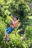 Niño pequeño sonriente feliz que monta una línea de la cremallera en un bosque tropical enorme imagen de archivo