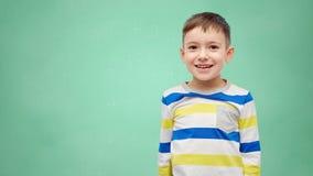 Niño pequeño sonriente feliz sobre consejo escolar verde Fotos de archivo