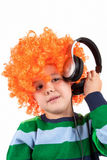 Niño pequeño sonriente que escucha la música en headphon Imagen de archivo libre de regalías