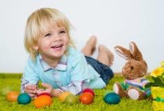 Niño pequeño sonriente que miente con los huevos de Pascua en la alfombra verde Fotos de archivo