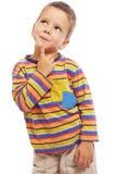 Niño pequeño sonriente que piensa alrededor Imagen de archivo libre de regalías