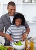 Niño pequeño sonriente que prepara la ensalada con su padre Foto de archivo libre de regalías