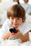Niño pequeño sonriente que sostiene un telecontrol Fotografía de archivo