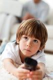 Niño pequeño sonriente que sostiene un telecontrol Fotos de archivo