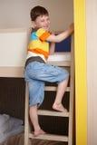 Niño pequeño sonriente que va para arriba la escala de la cama de cucheta imagen de archivo