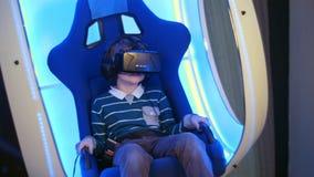 Niño pequeño sorprendido que experimenta realidad virtual en una silla interactiva móvil Fotografía de archivo