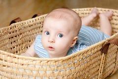 Niño pequeño sorprendido que miente en cesta de mimbre Foto de archivo libre de regalías