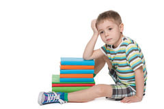 Niño pequeño triste cerca de los libros Imagenes de archivo