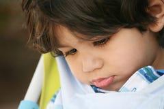 Niño pequeño triste con la pista abajo foto de archivo