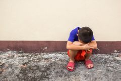 Niño pequeño triste que se sienta en piso en sitio vacío Foto de archivo