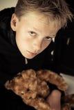 Niño pequeño triste que sostiene el juguete del oso de la felpa Foto de archivo